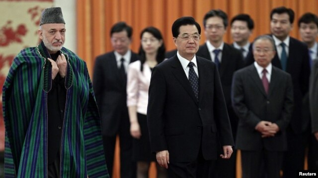 Chinese President Hu Jintao and his Afghan counterpart Hamid Karzai (L) attend a welcoming ceremony at the Great Hall of the People in Beijing June 8, 2012.
