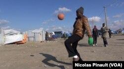 "Un migrant joue avec un ballon dans la ""Jungle"" de Calais, France (Nicolas Pinault/VOA)"