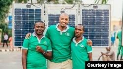 Le Rwandais Henri Nyakarundi (au centre), entouré de deux membres de son équipe, est l'inventeur du kiosque solaire, à Kigali, au Rwanda, le 25 janvier 2017.