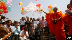 Buddhist monks, right, chant and pray during a rally in front of Royal Palace to call for the release of 23 detainees in Phnom Penh, file photo.