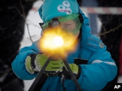 FILE - A boy to shoots a machine gun with blanks, at a weapon exhibition during a military show outside St.Petersburg, Russia, Jan. 15, 2017.