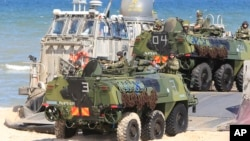FILE - Soldiers sit atop amphibious vehicles as NATO troops participate in the NATO sea exercises BALTOPS 2015, meant to reassure the Baltic Sea region allies in the face of a resurgent Russia, in Ustka, Poland, June 17, 2015.