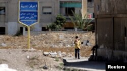 A boy stands near the entrance of the Waer district in the central Syrian city of Homs, Syria, Sept. 19, 2016.