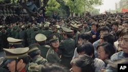 FILE - Students demonstrators scuffle with police as they try to break the guard line to march to the Tiananmen Square in Beijing, April 27, 1989.