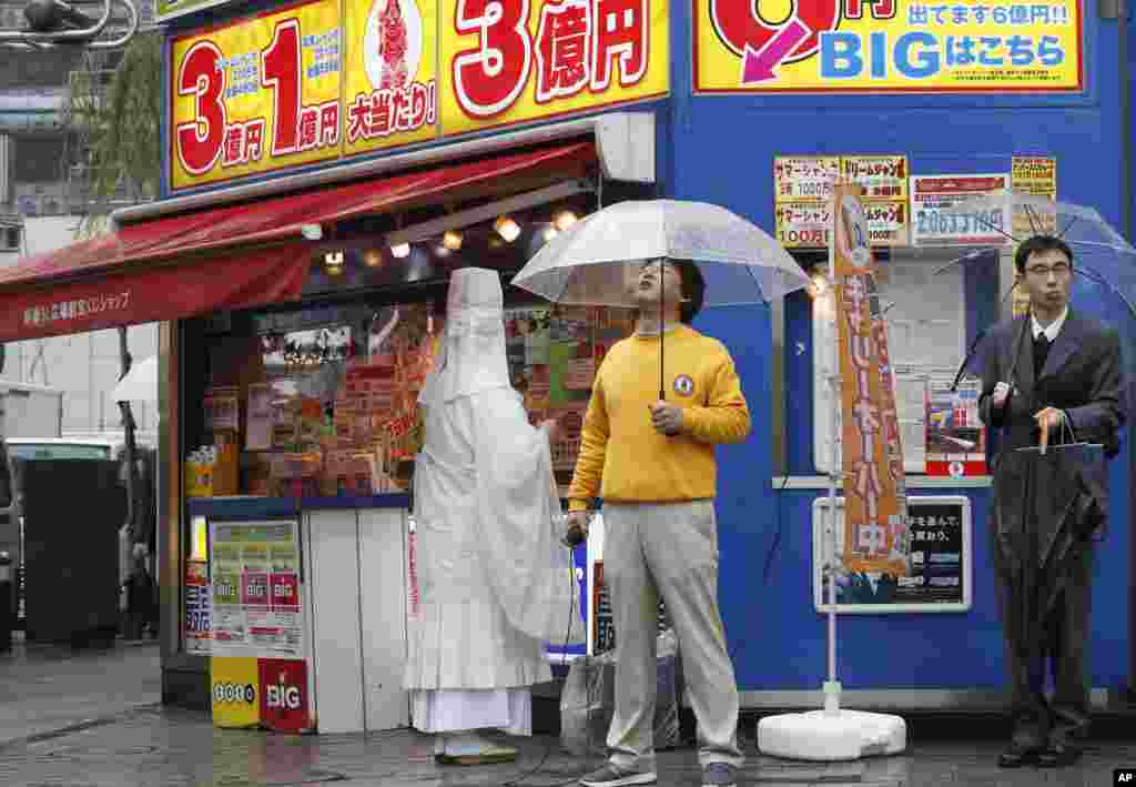 A monk chants a Buddhist mantra in front of a public lottery counter in Tokyo, Japan. Lottery stand owners hire monks to conduct ritual purification on their stands for a big win.