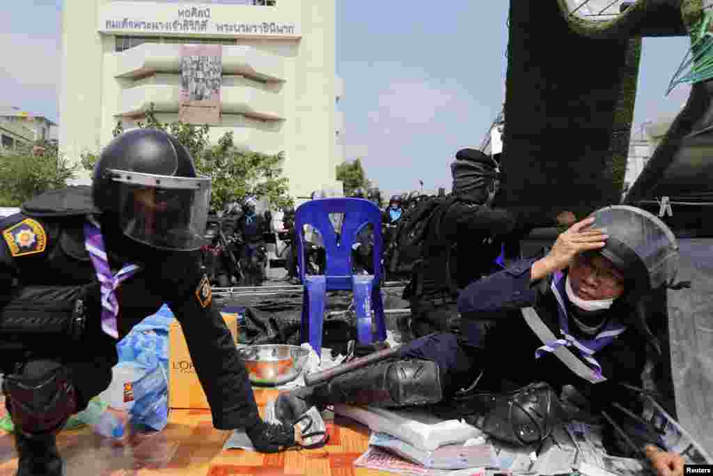 Policemen take cover as shots are fired during clashes with anti-government protesters near the Government House in Bangkok, Feb. 18, 2014.
