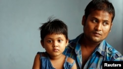 Abdul Rahim, seorang pengungsi Rohingya dari Myanmar, beserta putrinya Morja, dalam wawancara di rumah susun mereka di Kuala Lumpur , Mei 2013. (Reuters/Bazuki Muhammad)
