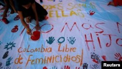 """FILE - Girls paint a banner during a demonstration to protest the violence against and killings of women, in Cartagena, Colombia, Oct. 27, 2016. The words at bottom left read: """"Colombia Femicide Free."""""""