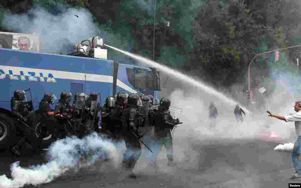 Anti-riot police use water cannon against protesters during a demonstration in Naples, Italy. Hundreds of protesters faced off riot police outside the Capodimonte Palace. The European Central Bank is holding on of its regular rate-setting meetings.