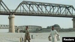 حیدرآباد کے قریب دریائے سندھ میں ریت اڑ رہی ہے جب کہ دو مقامی افراد کہیں دور سے پانی بھر کر لارہے ہیں (فائل فوٹو)