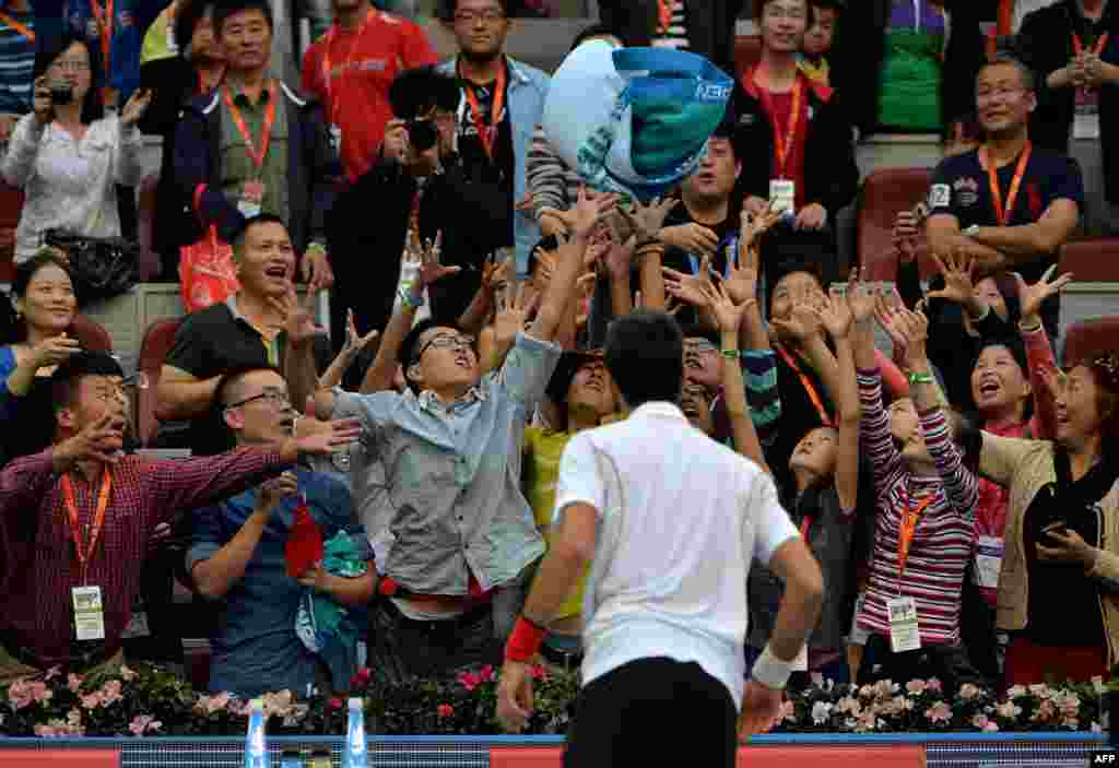 Serbia's Novak Djokovic throws a towel into the crowd after winning the men's singles match against Lukas Rosol of the Czech Republic at the China Open tennis tournament in Beijing, China. Djokovic won 6-0, 6-3.