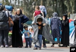 Migrants carrying their belongings walk in the Athens port of Piraeus, April 7, 2016.