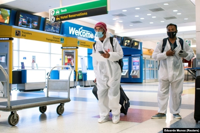 Para penumpang dari London tiba di Bandara Internasional JFK di New York, di tengah pembatasan baru untuk mencegah virus corona (COVID-19), 21 Desember 2020. (Foto: Eduardo Munoz/Reuters)