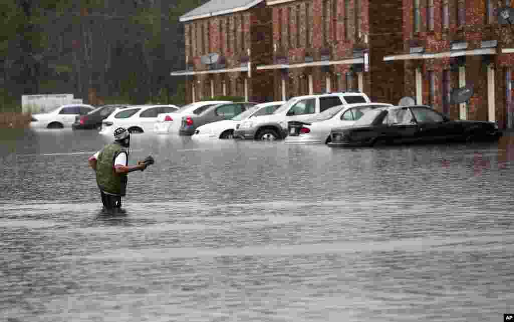 یک مرد در حین سیل لوئیزیانا به سختی از آب عبور می کند. چهار روز بارش باران، مردم را در این ایالت جنوبی آمریکا دچار مشکل کرد.