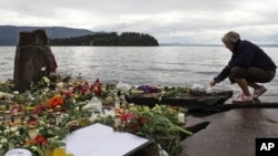 FILE - A woman lights a candle in Sundvollen, facing Utoya island, where gunman Anders Behring Breivik killed at least 68 people, near Oslo, Norway, July 26, 2011. A court ruled last week that Breivik was being subjected to inhumane prison conditions.
