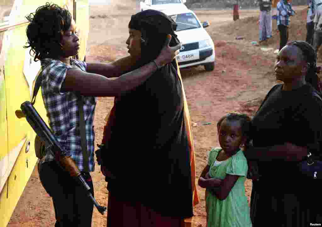 A plainclothes policewoman searches female passengers, travelling to Nairobi, for weapons in the town of Mandera at Kenya-Somalia border.