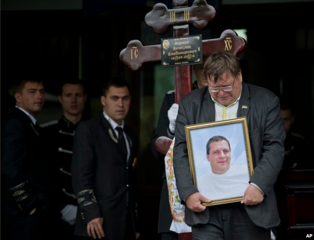 A mourner carries the picture of regional parliament member Vyacheslav Markin, in Odessa, Ukraine, May 5, 2014. Markin, who was known for speaking out against the government in Kyiv.
