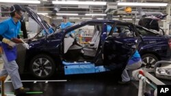 In this Oct. 30, 2017, photo, workers of a Toyota Motor Corp. assemble a Mirai fuel cell vehicle at the automaker's Motomachi plant in Toyota, western Japan. (AP Photo/Yuri Kageyama)