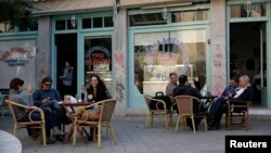 People sit at a cafe at a central square in Nicosia, March 29, 2013.