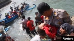A police officer carries an unconscious child who was on the boat that capsized after hitting a reef off the coast of Sukapura, at Jayanti beach in Indonesia's West Java province on July 24, 2013.