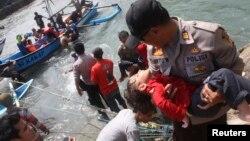 Cảnh sát Indonesia bế một đứa bé bất tỉnh được cứu từ chiếc thuyền bị lật ngoài khơi Indonesia, 24/7/13