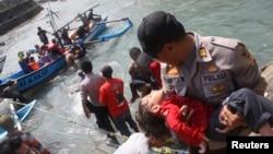 ຕຳຫຼວດ ອູ້ມເດັກນ້ອຍຄົນນຶ່ງ ທີ່ໝົດສະຕິໄປ ຈາກເຮືອ ພວກທີ່ຊອກຫາບ່ອນລີ້ໄພ ທີ່ແລ່ນໄປຕຳໂງ່ນຫີນ ແລ້ວກໍຫຼົ້ມ ຢູ່ນອກແຄມຝັ່ງ Sukapura ໃນເຂດເມືອງ Cianjur ແຂວງ Java ຕາເວັນຕົກ ຂອງອິນໂດເນເຊຍ (24 ກໍລະກົດ 2013)