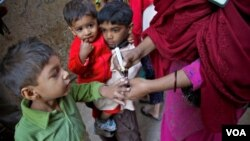 ایک ہیلتھ ورکر بچے کو پولیو کے قطرے پلانے کے بعد اس کے ہاتھ پر شناختی نشان لگا رہی ہے۔ فائل فوٹو