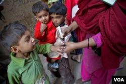 کراچی کی ایک مضافاتی آبادی میں ایک پولیو ورکر بچوں کو ویکیسن کے قطرے پلانے کے بعد نسان لگا رہی ہے۔ فائل فوٹو