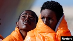 Migrants stand in line after disembarking from the Norwegian vessel Siem Pilot at Pozzallo's harbor, Italy, March 29, 2016.