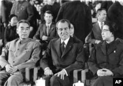 FILE - President Nixon sits between Chinese Premier Chou En-lai and Chiang Ching, wife of Chairman Mao Tse-tung, at a cultural show in the Great Hall of the People, Feb. 22, 1972 in Peking as an interlude in the talks between the two countries leaders.