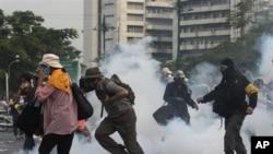 Polisi menembakkan gas air mata ke arah demonstran yang berusaha menerobos barikade (foto, 24/11/2012).