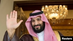 FILE - Saudi Crown Prince Mohammed bin Salman waves as he meets with a visiting official in Riyadh, Saudi Arabia, April 11, 2017.