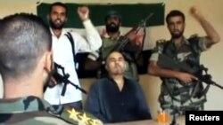 Pemberontak Suriah merilis video seorang pilot Suriah yang tertangkap, Kolonel Rafik Mohammed Suleiman (tengah).