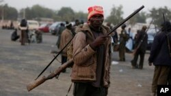 FILE - Boko Haram fighters have sized a multinational military base in the Nigerian town of Baga. In some areas where the Islamist extremists have been active, local hunters and vigilantes have taken up arms to defend themselves.