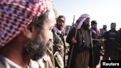FILE - Yazidi fighters gather on the summit of Mount Sinjar as they head to battle Islamic State militants, in Iraq, Dec. 21, 2014. IS swept into Sinjar town and surrounding villages in early August; many residents were from the Yazidi religious community.