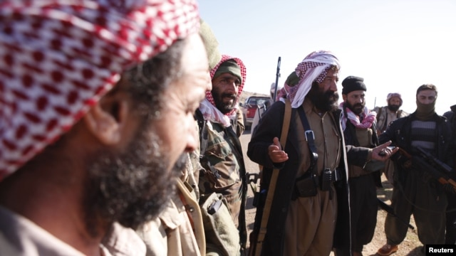 FILE - Yazidi fighters gather at Mount Sinjar as they head to battle Islamic State militants in Iraq, Dec. 21, 2014. IS swept into Sinjar town and surrounding villages in early August; hundreds of Yazidi women and girls were taken captive and turned into sex slaves.