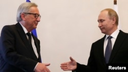 Russian President Vladimir Putin, right, approaches to shake hands with European Commission President Jean-Claude Juncker during a meeting in St. Petersburg, Russia, June 16, 2016.