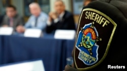 FILE - Law enforcement from Hennepin county, Minnesota takes part in a round table discussion on ways to reduce gun violence during a visit to the Minneapolis.