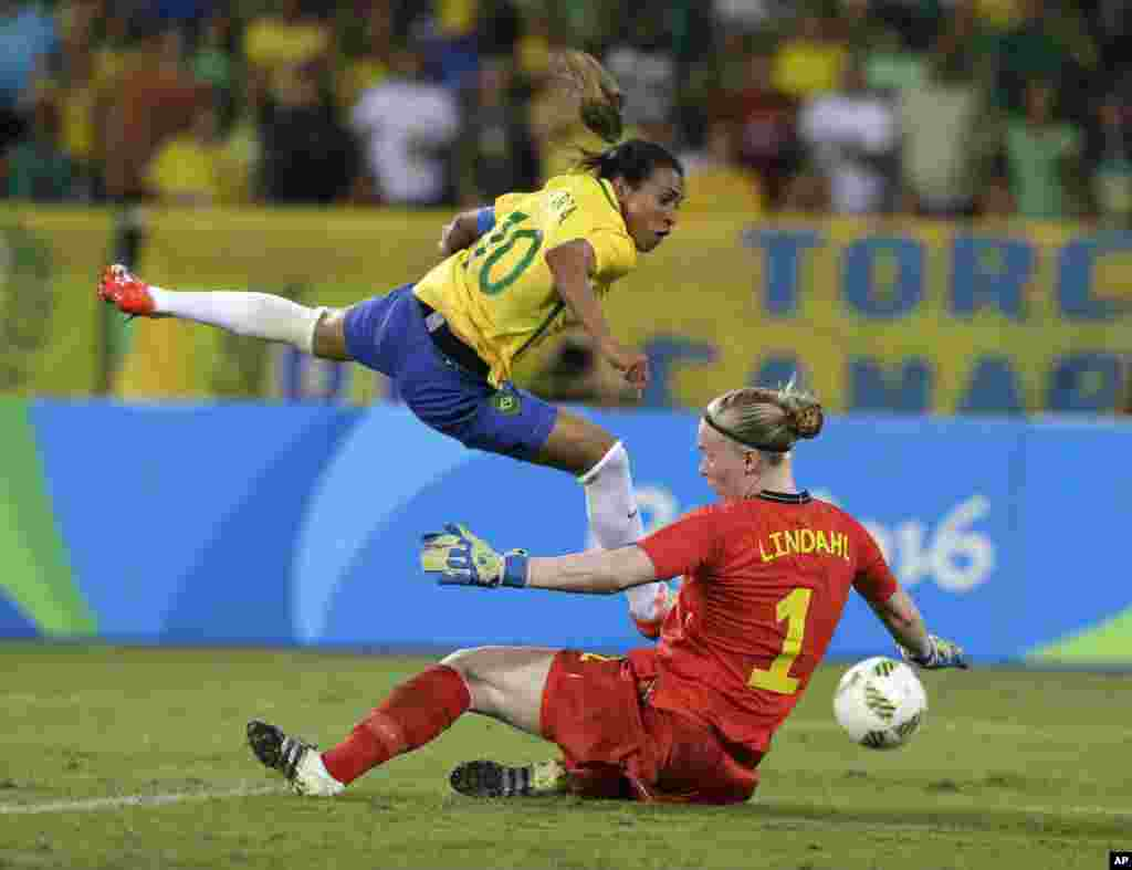 Brazil's Marta, left, leaps over Sweden goalkeeper Hedvig Lindahl as she attempts a shot on goal during a group E match of the women's Olympic football tournament between Sweden and Brazil at the Rio Olympic Stadium.