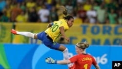 Rio Olympics Soccer Women: Brazil's Marta, left, leaps over Sweden goalkeeper Hedvig Lindahl as she attempts a shot on goal during a group E match of the women's Olympic football tournament between Sweden and Brazil at the Rio Olympic Stadium in Rio De Ja