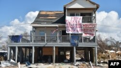 """A sign that reads """"FEMA please help make Mexico Beach great again"""" is seen on a damaged house by Hurricane Michael in Mexico Beach, Florida, on Oct. 15, 2018."""