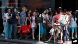 FILE - Chinese tourists line up to enter a fashion store in Paris Aug. 12, 2015. (AP Photo/Francois Mori)