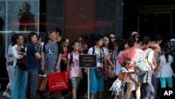 Khách du lịch xếp hàng để vào thăm một cửa hàng thời trang ở Paris.