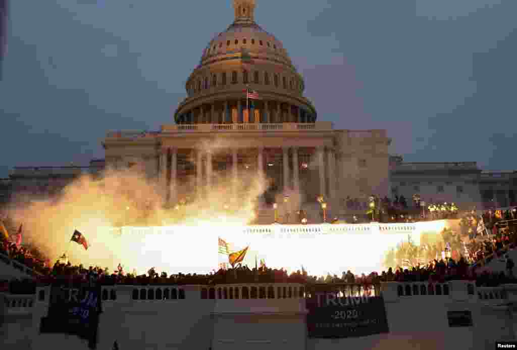 An explosion caused by a police munition is seen while supporters of U.S. President Donald Trump gather in front of the Capitol Building in Washington, D.C., Jan. 6, 2021.