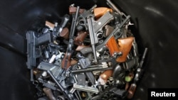 Hand guns turned in by their owners lie in a trash bin in Los Angeles. The Los Angeles Police Department held a buy-back to get guns off the street. The program to buy guns followed the mass shooting at Sandy Hook Elementary School in Connecticut on December 26, 2012.