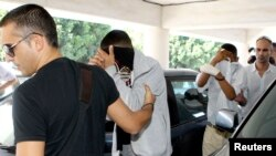 Police escort two of three British tourists suspected of stabbing an off-duty British solider to a court in Paralimni, November 5, 2012.