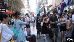 福建赴港大陸自由行旅客陳小姐(持手機拍攝者)及謝小姐(揹著黃色包包)表示,遇上反大陸自由行遊行,不會減少她們再次到香港旅遊的意欲(美國之音湯惠芸)