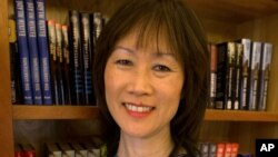 FILE - In this Nov. 5, 2002 file photo, Tess Gerritsen, an author and one of the biggest names in the medical thriller genre, stands in the library at her home in Camden, Maine.