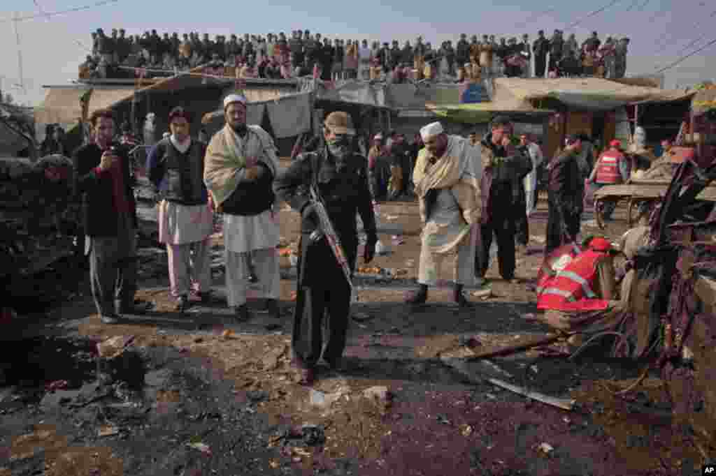 Residents look on as security officials and rescue workers go through the site of a bomb explosion in Jamrud bazaar, about 25 km (15 miles) west of Peshawar in northwest Pakistan, January 10, 2012. (Reuters)