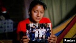 Norma Méndez, esposa del migrante salvadoreño Marvin González, quien murió en un centro de detención en Nuevo México, muestra fotos de Marvin en su casa de Verapaz, El Salvador, el 2 de agosto de 2019. REUTERS/José Cabezas.